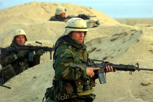 Three soldiers in a sand dune, holding weapons