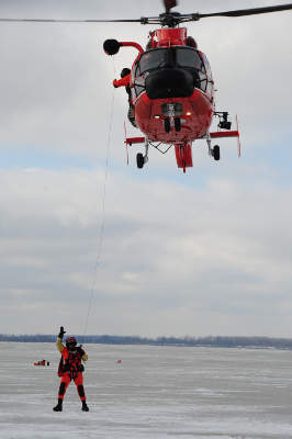An MH-65C Short Range Recovery (SRR) helicopter deploys a rescue swimmer during the Icy Resolve 2013 mass rescue full-scale exercise. Image courtesy of US Coast Guard photo by Petty Officer 2nd Class Levi Read.