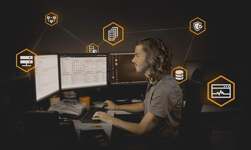 man looking at computer screen in dark